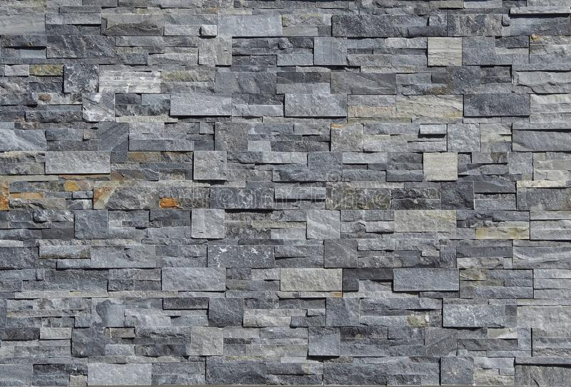 灰色石墙金属被堆积的由小条和方形块做成 背景和纹理 免版税库存图片