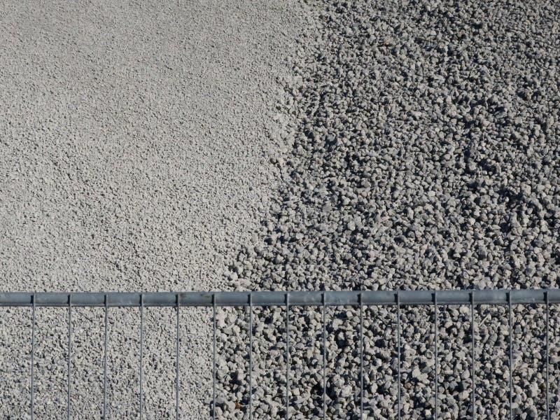 灰色石渣或沙粒在一个沙坑在篱芭后 免版税库存照片