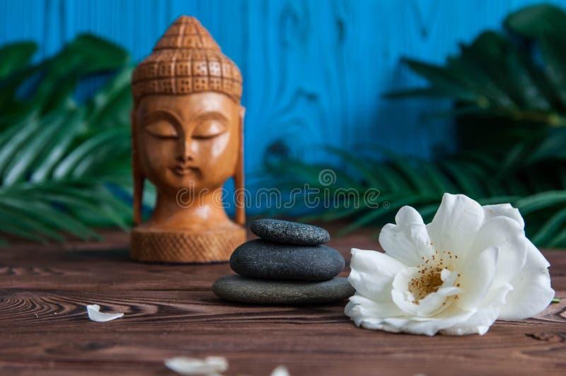 灰色禅宗石头金字塔与白花,绿色的在木背景离开 和谐、平衡和凝思的概念, 库存图片