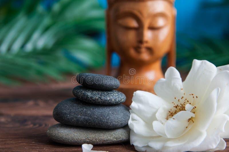 灰色禅宗石头金字塔与白花,绿色的在木背景离开 和谐、平衡和凝思的概念, 库存照片