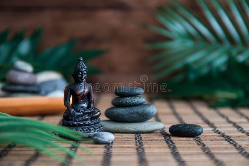 灰色禅宗石头金字塔与绿色叶子和菩萨雕象的 和谐、平衡和凝思,温泉,按摩的概念,放松 图库摄影