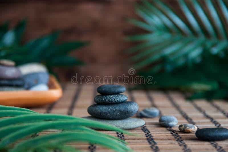 灰色禅宗石头金字塔与绿色叶子和菩萨雕象的 和谐、平衡和凝思,温泉,按摩的概念,放松 免版税库存照片