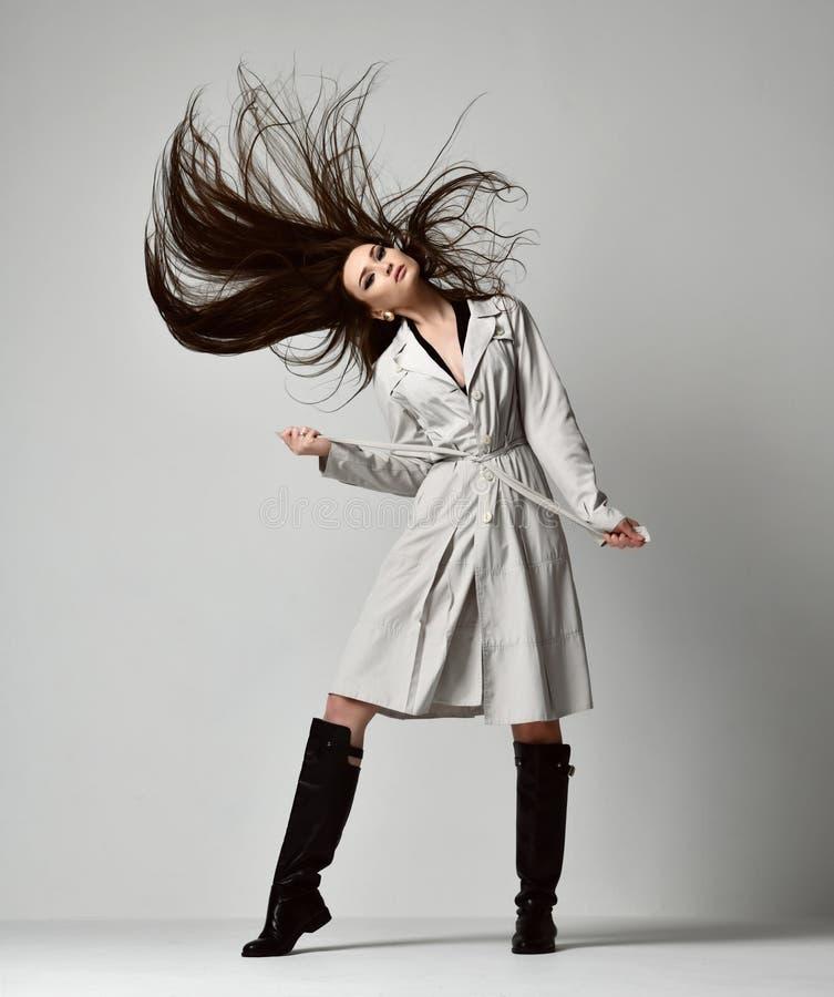 灰色秋天夹克的美丽的深色的行家妇女有摆在充分的身体的有风头发的 免版税库存图片