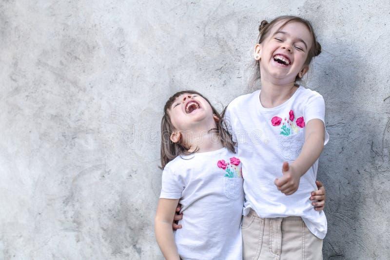 灰色织地不很细背景的快乐的女孩 室外画象女孩 灰色织地不很细墙壁背景 图库摄影