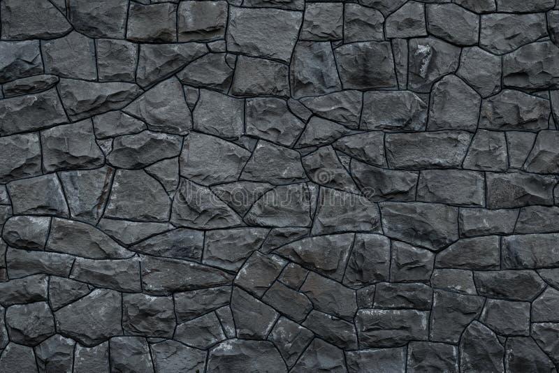 灰色肮脏的石墙 灰色花岗岩纹理  黑暗的概略的岩石背景 被风化的深灰难看的东西大厦的门面 ??s 库存照片