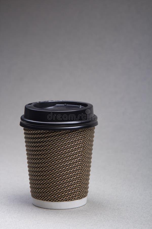 灰色背景中咖啡卡布奇诺的纸杯特写 免版税库存图片