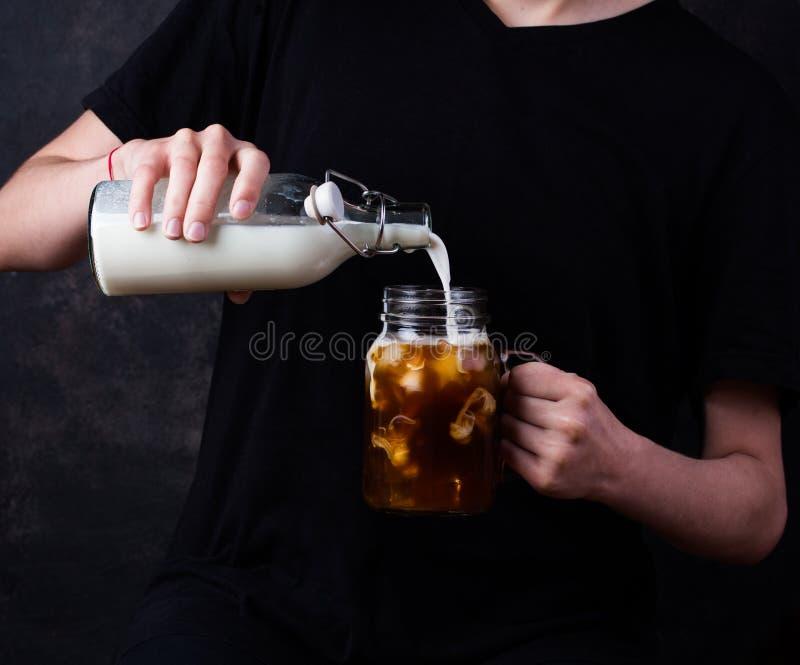 灰色背景中拿着冰咖啡和牛奶的玻璃杯女子 免版税库存照片