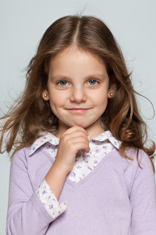 灰色背景的俏丽的微笑的女孩 库存照片