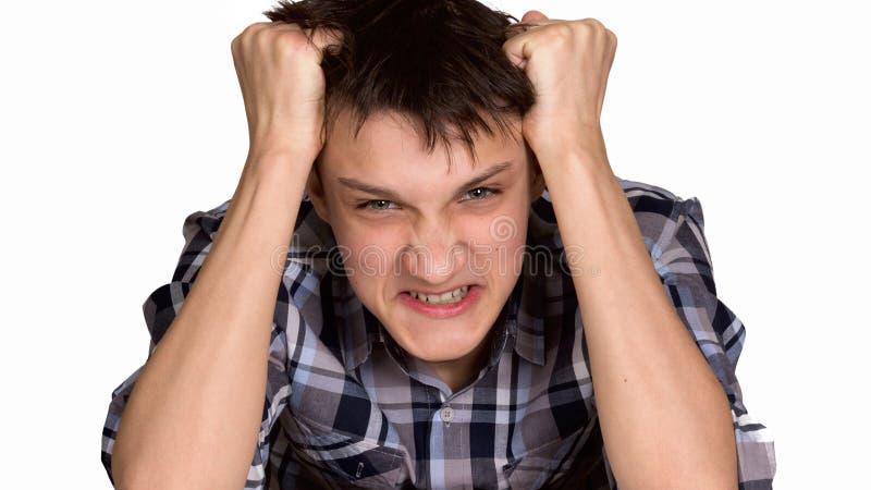 灰色背景的脾气坏的年轻人 免版税图库摄影