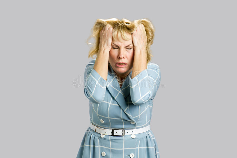 灰色背景的绝望成熟妇女 免版税库存照片