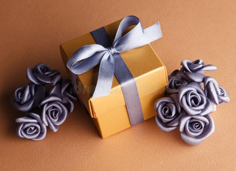 灰色花和金黄礼物盒 免版税库存图片