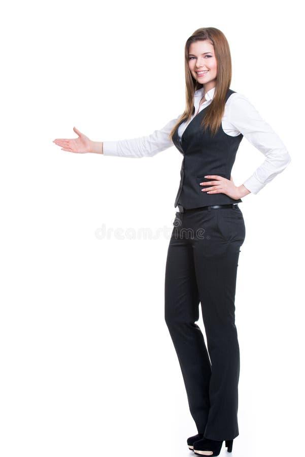 灰色衣服的愉快的妇女指向某事的。 免版税库存图片