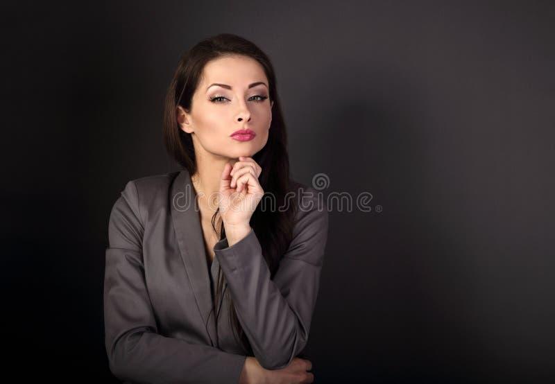 灰色衣服的美丽的严肃的女商人认为在黑暗的g的 免版税库存照片