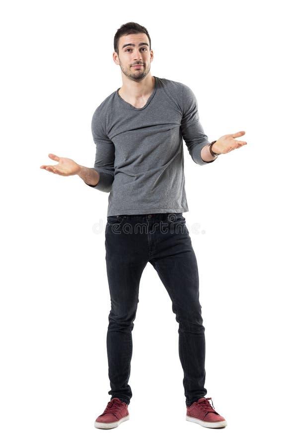 灰色衬衣的困惑的年轻人耸肩与开放胳膊的查寻 库存照片