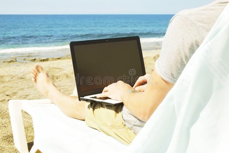 灰色衬衣的年轻人在海滩,运作坐膝上型计算机 博客作者,作家,编码人,遥远的工作者冲浪的浏览researchin 免版税库存照片