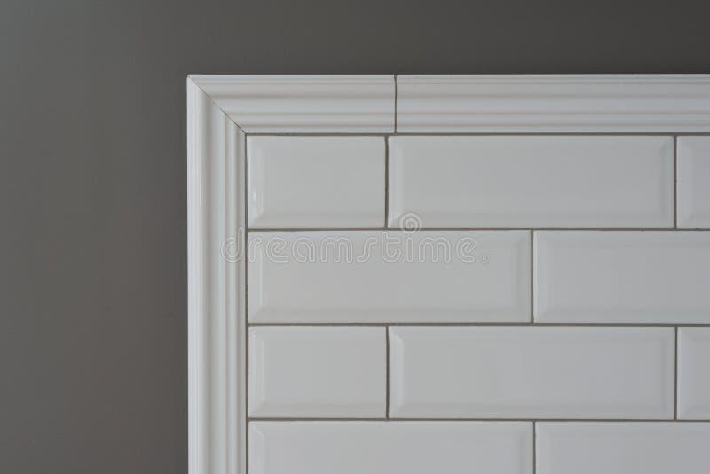 灰色被绘的墙壁,一部分的墙壁是被盖的瓦片小白色光滑的砖,陶瓷装饰造型瓦片, intrica细节  免版税图库摄影
