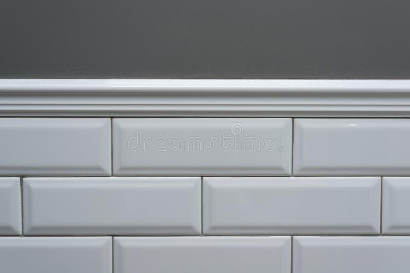 灰色被绘的墙壁,一部分的墙壁是被盖的瓦片小白色光滑的砖,陶瓷装饰造型瓦片 w的片段 库存照片