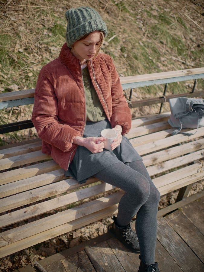 灰色裙子和裤袜的一名妇女,穿一个绿色帽子和一件红色夹克,坐长凳和饮料茶 库存照片