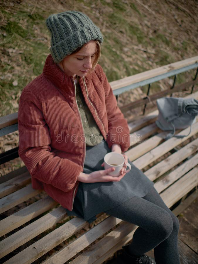 灰色裙子和裤袜的一名妇女,穿一个绿色帽子和一件红色夹克,坐长凳和饮料茶 免版税库存图片