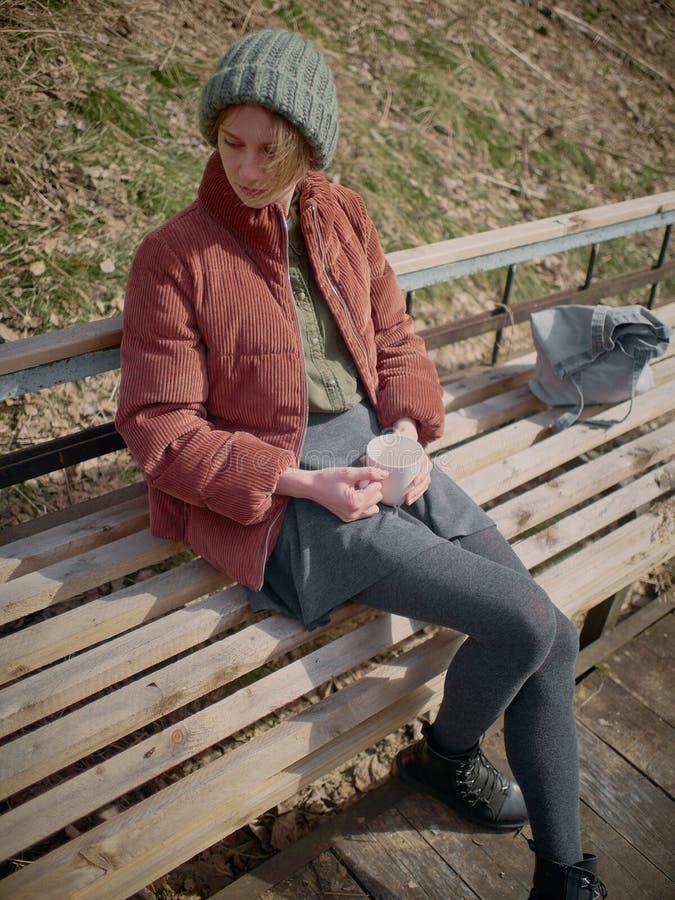 灰色裙子和裤袜的一名妇女,穿一个绿色帽子和一件红色夹克,坐长凳和饮料茶 库存图片