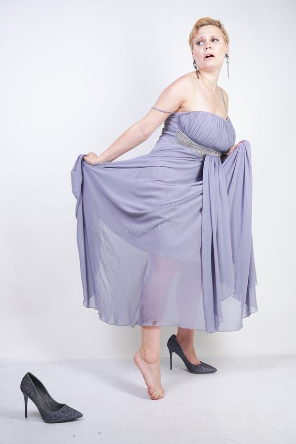 灰色褂子礼服的迷人的正大小年轻女人在演播室丢失了在白色背景的拖鞋 美丽的胖的短发白肤金发的g 库存图片