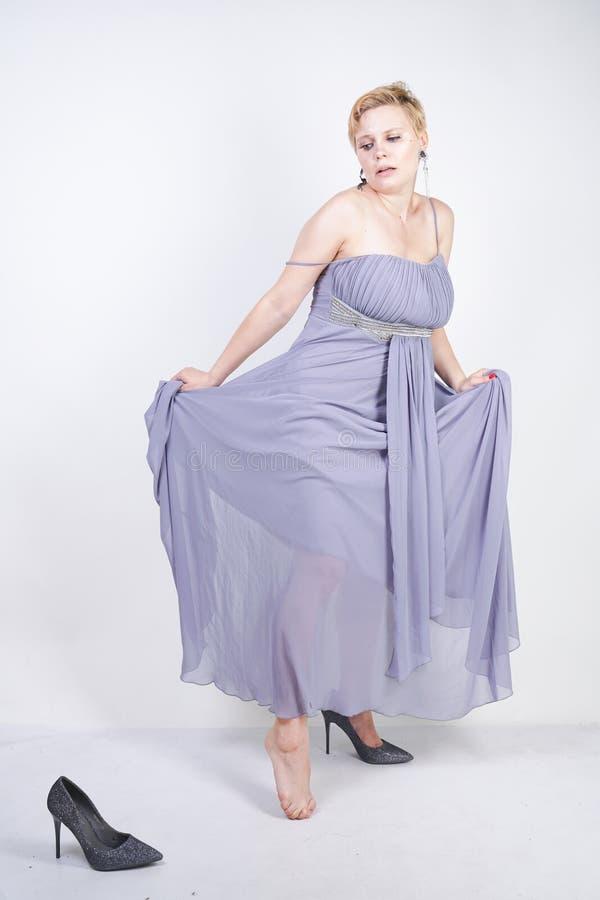 灰色褂子礼服的迷人的正大小年轻女人在演播室丢失了在白色背景的拖鞋 美丽的胖的短发白肤金发的g 免版税库存图片