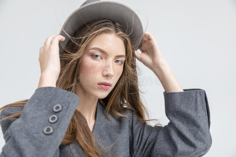 灰色调整的帽子的逗人喜爱的年轻女人 库存图片