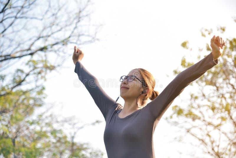 灰色运动服锻炼的亚裔女性在公园 库存图片