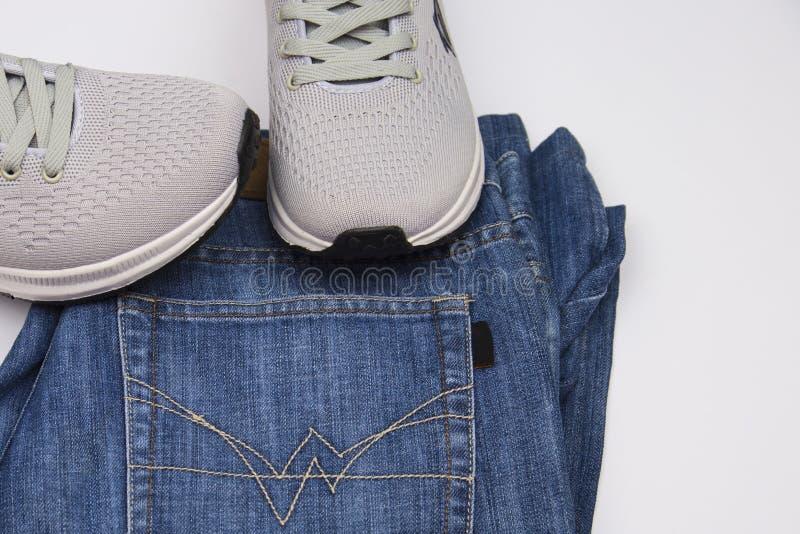 灰色运动鞋和牛仔裤 走的衣物 旅行的衣物 运动鞋和蓝色牛仔裤 在白色背景的人的鞋子 库存照片