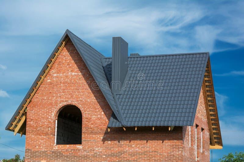 灰色金属瓦片屋顶建筑和大厦新的砖Hous 免版税库存照片