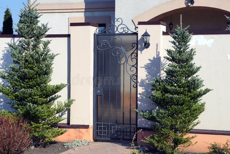 灰色金属门和白色具体篱芭在街道上有绿色针叶树的 库存照片
