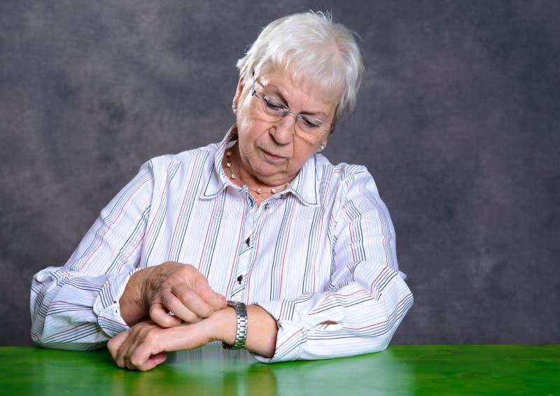 灰色长毛的年长妇女设置了她的手表 库存图片