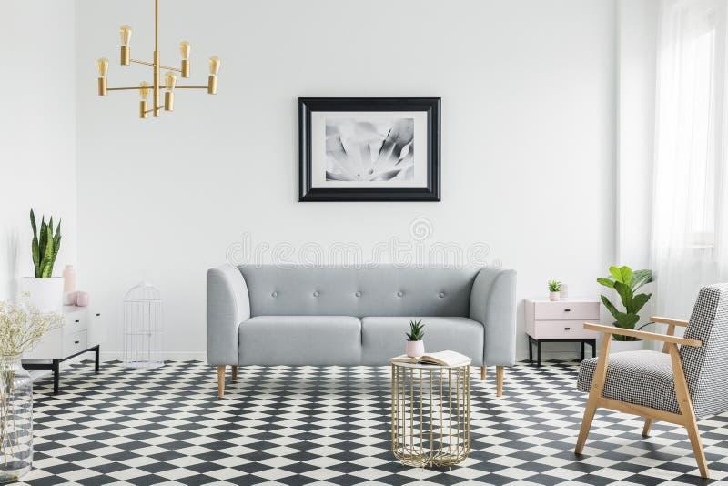 灰色长沙发和扶手椅子在方格的地板上在白色平的内部与金灯和海报 实际照片 库存照片