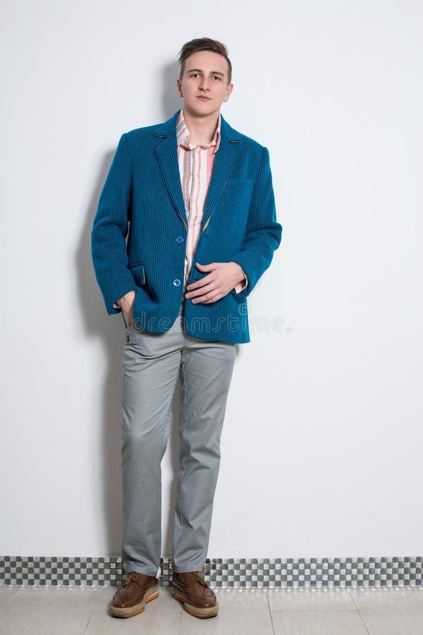 灰色长裤和一件深蓝夹克的人 库存图片