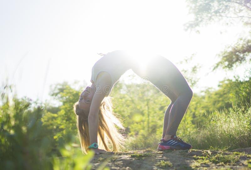 灰色顶面实践的瑜伽的少妇在美好的自然 Str 库存图片