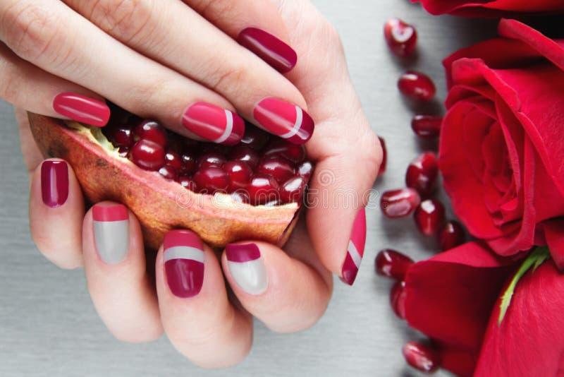 灰色,桃红色和红色非对称钉子艺术修指甲 库存图片