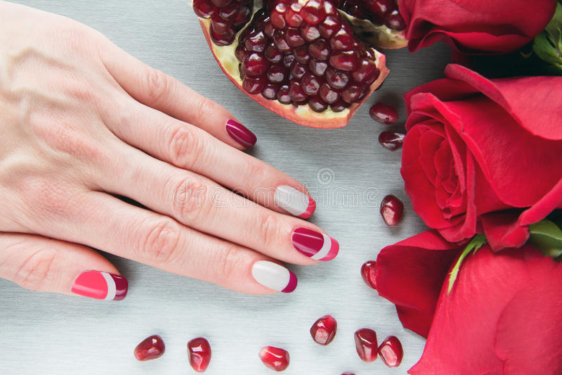 灰色,桃红色和红色非对称钉子艺术修指甲 免版税库存照片