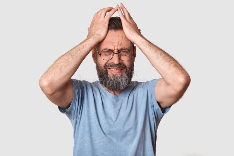 灰色T恤杉的有胡子的人,有圆的eyewear,保留在头的手,做鬼脸,有问题,是在心情,有可怕 库存图片
