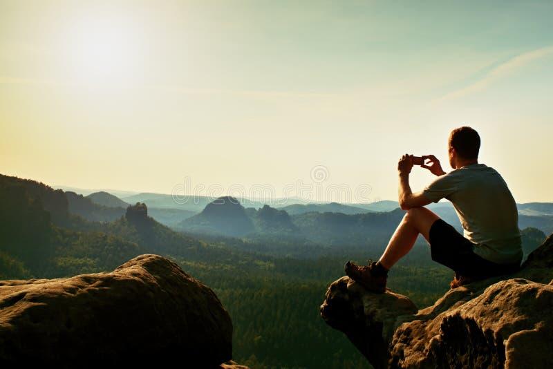 灰色T恤杉的游人拍与巧妙的电话的照片在岩石峰顶  下面梦想的多小山风景,橙色桃红色有薄雾的日出 库存照片