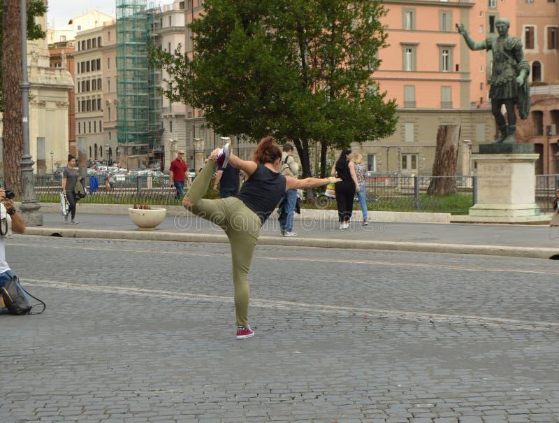 灵活的行家女孩在一个常设姿势平衡,弯曲她的腿后面 摆在前面的一张照片写真的 免版税库存照片