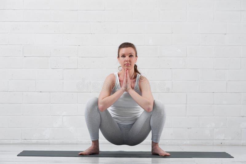 年轻灵活的在灰色席子的女子实践的瑜伽 免版税图库摄影