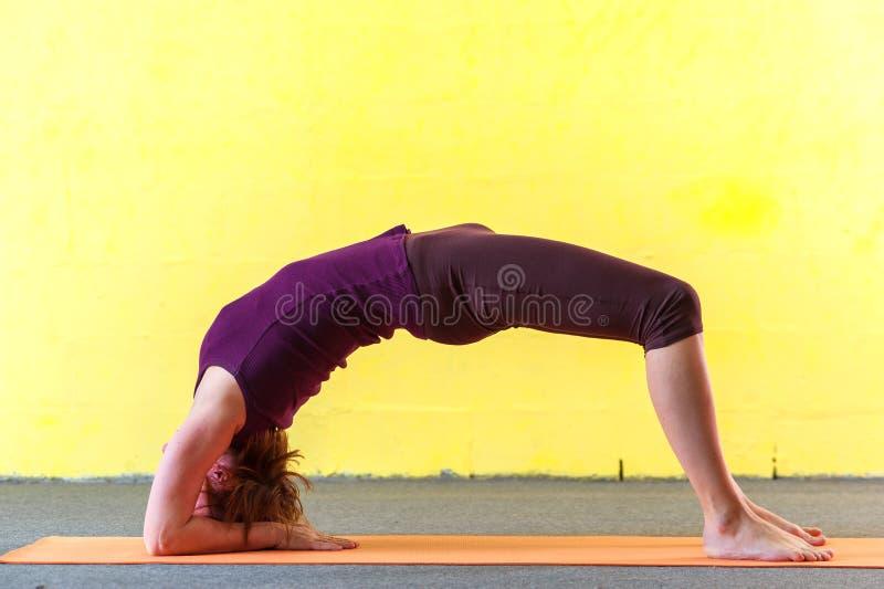 年轻灵活的在类的女子实践的瑜伽 库存图片