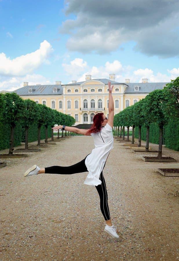 年轻灵活的红头发人妇女跳舞芭蕾在宫殿公园 库存图片