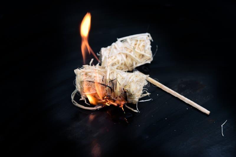 灼烧的刨花烤在一个黑金属碗的打火机,复制s 免版税库存照片