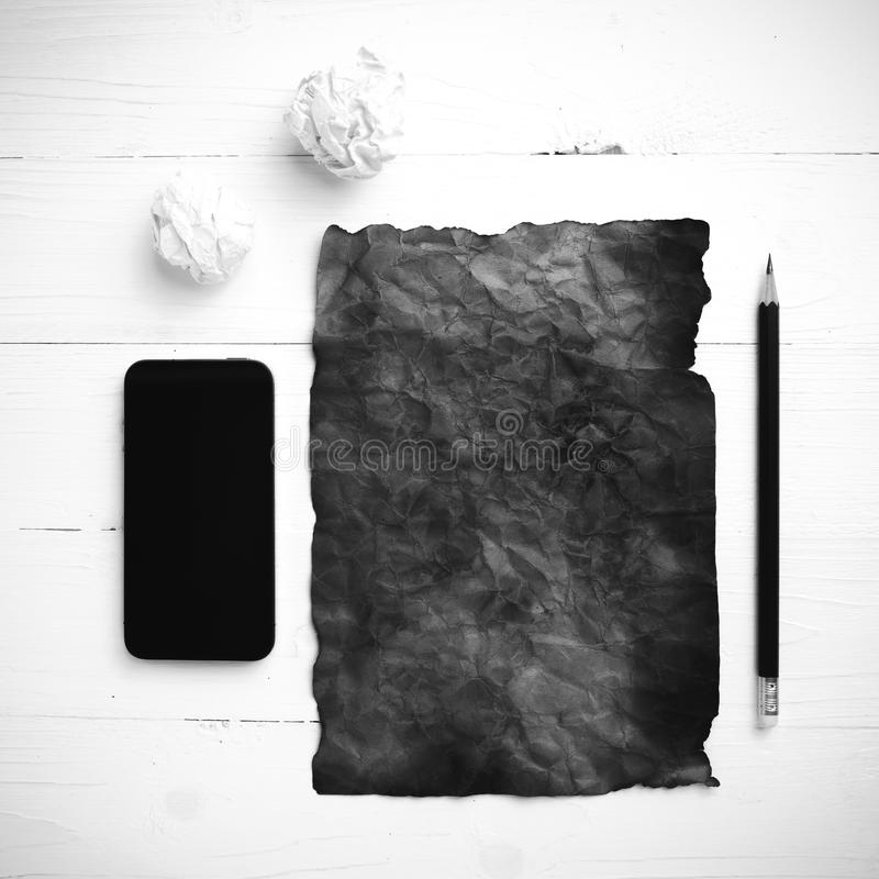 灼烧的包装纸和被弄皱的纸与聪明的电话的黑色 图库摄影