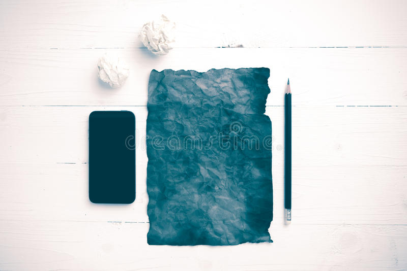 灼烧的包装纸和被弄皱的纸与聪明的电话葡萄酒 库存照片