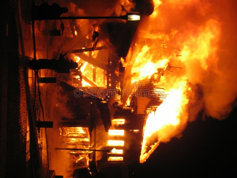灼烧的战斗消防队员房子 免版税库存照片