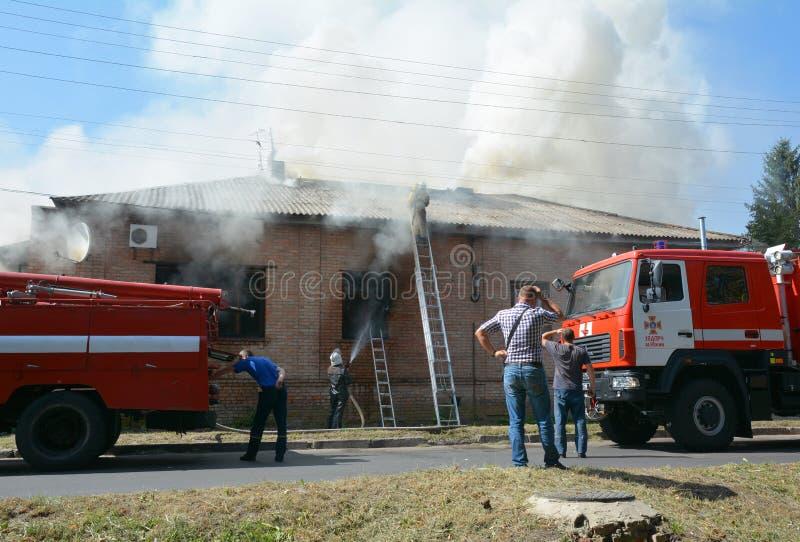灼烧的房子 红色救火车、火灾损失房子和消防队员 议院烧毁 免版税库存图片