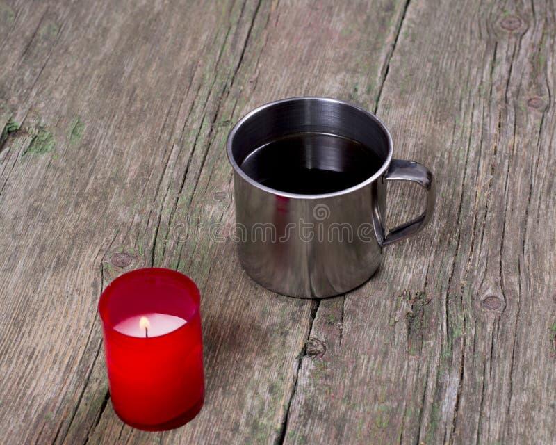 灼烧的红色蜡烛和钢咖啡 免版税库存图片