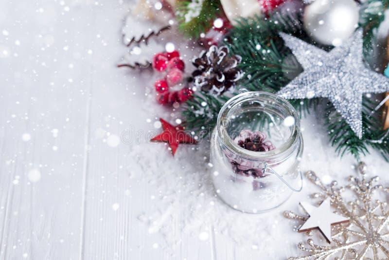 灼烧的蜡烛和圣诞节装饰在雪和木背景,典雅的低调射击充满欢乐心情 免版税图库摄影
